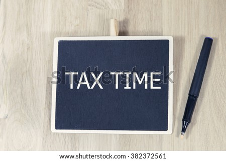 sentence tax time written with pen on a blackboard, on a wooden table  - stock photo
