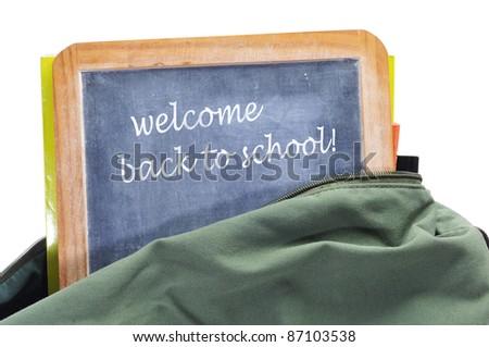 sentence welcome back to school written in a blackboard in a school bag with books - stock photo