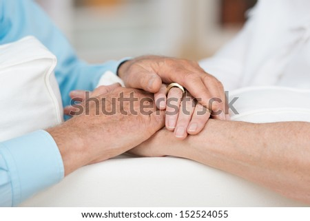 Sentimental conceptual image of love, commitment and support between two elderly people as they tenderly hold hands, close up view - stock photo