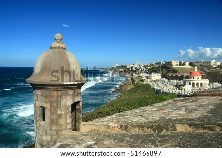 Sentry box overlooking the Atlantic Ocean at 'El Morro' (Castillo San Felipe del Morro) and the La Perla district of Old San Juan, Puerto Rico, including an old cemetery - stock photo