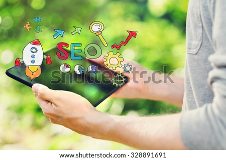 SEO concept with young man holding his tablet computer outside in the park - stock photo