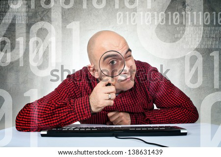 SEO engineer or computer search concept. Man sitting at the computer table with keyboard holding magnifying glass.
