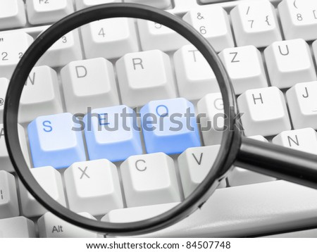SEO - search engine optimization concept with the letters s, e, o on a computer keyboard seen through a magnifying glass - stock photo
