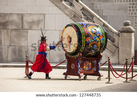 SEOUL, KOREA - APRIL 27: A guard strikes a giant ceremonial drum during the changing of the guard ceremony at the Gyeongbokgung Palace complex in Seoul, Korea on April 27, 2012. - stock photo