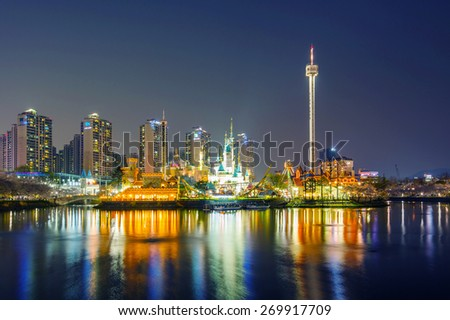 SEOUL, KOREA - APRIL 9, 2015: Lotte World amusement park at night and cherry blossom of Spring, a major tourist attraction in Seoul, South Korea on April 9, 2015