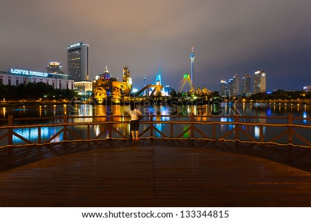 SEOUL, KOREA - AUGUST 26, 2009: An unidentified woman admires the reflected night lights at Lotte World amusement park, a major tourist attraction in Seoul, South Korea on August 26, 2009 - stock photo