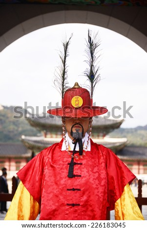 SEOUL, KOREA - OCTOBER 22 : Korean guard dressed in a red uniform stands at the entrance to the Gyeongbokgung Palace in Seoul, Korea on October 22, 2014. - stock photo