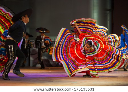 SEOUL, KOREA - SEPTEMBER 30, 2009: A female Mexican dancer spins her colorful traditional dress in front of her partner at a traditional folkloric dance performance at city hall's open-air stage - stock photo