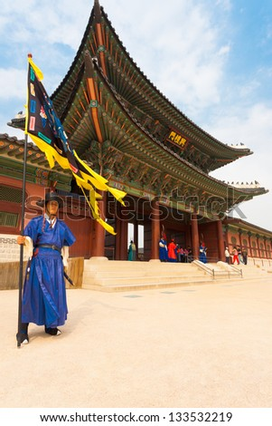 SEOUL, KOREA - SEPTEMBER 17, 2009: A flag guard in ancient blue Korean costume stands at the entry gate of Gyeongbokgung Palace, the old royal residence, in Seoul, South Korea on September 17, 2009 - stock photo