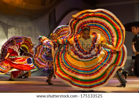 Seoul, Korea - September 30, 2009: Beautiful female Mexican dancer dancing, spinning and spreading her colorful yellow dress during a traditional folk show at a public outdoor stage at city hall - stock photo