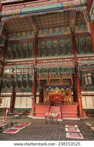 SEOUL, SOUTH KOREA - APRIL 27, 2012: The royal throne room in the interior of Geunjeongjeon Hall in the Gyeongbokgung Palace complex is covered with ornate bright red and green decorations. - stock photo