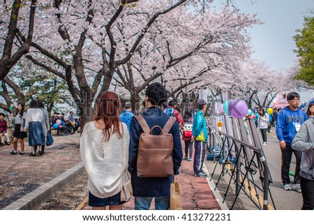 SEOUL, SOUTH KOREA APRIL 10,2016:YEONGDEUNGPO YEOUIDO PARK,couple are walking on the road park around colorful cherry blossom festival.