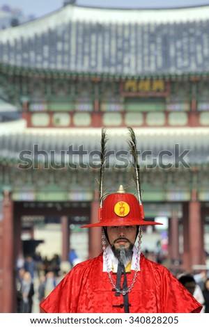 SEOUL, SOUTH KOREA - NOVEMBER 8, 2015: Armed guard in traditional costume guard the entry gate at Deoksugung Palace, a tourist landmark, in Seoul. November 8, 2015 Seoul, South Korea - stock photo