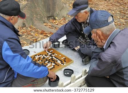 SEOUL, SOUTH KOREA-NOVEMBER 15: Men playing in the outside Baduka that is the Korean name for Go. November 15, 2015 Seoul, South Korea   - stock photo