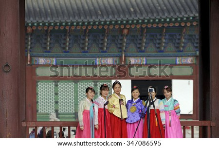 SEOUL,SOUTH KOREA-NOVEMBER 11:Teenagers in traditional costume taking a selfie in front of the Gyeongbokgung Palace. November 11, 2015 Seoul, South Korea - stock photo