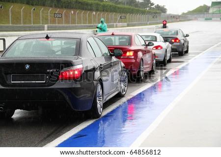 SEPANG - CIRCA MAY 2010: Anonymous BMW car owners test drive their cars at Sepang race track, Malaysia, during a rainy HPC track day circa May 2010. - stock photo