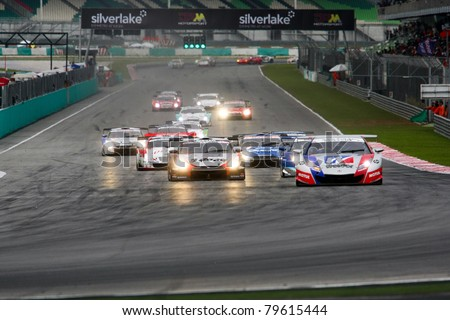 SEPANG - JUNE 19: Cars take off from a rolling start at the Japan SUPER GT Round 3 race at the Sepang International Circuit on June 19, 2011 in Sepang, Malaysia. The GT500 cars start in the front. - stock photo
