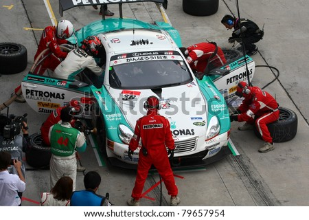 SEPANG - JUNE 19: Lexus Team Petronas Tom's pit crew prepares to refuel and change tires during a pit-stop of the Japan SUPER GT Round 3 race on June 19, 2011 in Sepang International Circuit, Malaysia - stock photo