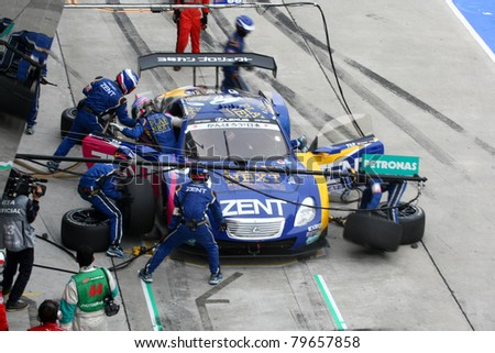 SEPANG - JUNE 19: Lexus Team Zent Cerumo's pit crew prepares to refuel and change tires during a pit-stop of the Japan SUPER GT Round 3 race on June 19, 2011 in Sepang International Circuit, Malaysia. - stock photo