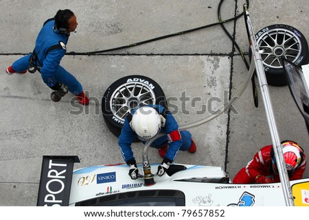 SEPANG - JUNE 19: LMP Motorsport pit crew prepares to refuel and change tires during a pit-stop of the Japan SUPER GT Round 3 race on June 19, 2011 in Sepang International Circuit, Malaysia. - stock photo