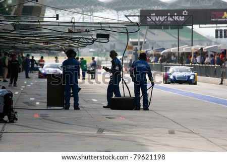 SEPANG - JUNE 19: Team Impul's pit-crew waits for their car to come in during the practice round of the Japan SUPER GT Round 3 race on June 19, 2011 in Sepang international Circuit, Malaysia. - stock photo