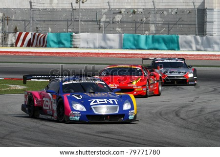 SEPANG - JUNE 19: The race car of Lexus Team Zent Cerumo moves into turn 2 closed followed by others during the Japan SUPER GT Round 3 race on June 19, 2011 in Sepang International Circuit, Malaysia. - stock photo