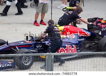 SEPANG, MALAYSIA - APRIL 8: Australian Mark Webber of Red Bull Racing being pushed back into the pit garage after Friday practice at Petronas Formula 1 Grand Prix on April 8, 2011 in Sepang, Malaysia - stock photo