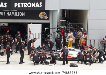 SEPANG, MALAYSIA - APRIL 8: British Jenson Button of McLaren having a trial pitstop during Friday practice at Petronas Formula 1 Grand Prix on April 8, 2011 in Sepang, Malaysia - stock photo