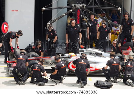 SEPANG, MALAYSIA - APRIL 8: British Lewis Hamilton of McLaren having a trial pitstop during Friday practice at Petronas Formula 1 Grand Prix on April 8, 2011 in Sepang, Malaysia - stock photo