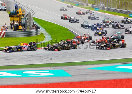 SEPANG, MALAYSIA - APRIL 10: Cars race around the corner on the first lap at the Formula 1 GP, on April 10, 2011 in  Sepang, Malaysia. - stock photo