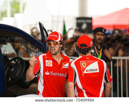 SEPANG, MALAYSIA - APRIL 10: Fernando Alonso and Felipe Massa (Ferrari) greet fans at the  autograph session on Formula 1 GP, April 10 2011, Sepang, Malaysia - stock photo