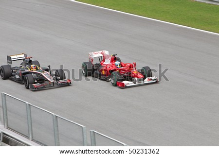 SEPANG, MALAYSIA - APRIL 4: Indian Karun Chandhok of Team Lotus being overtaken by Spanish Fernando Alonso at the Petronas Formula 1 Grand Prix April 4, 2010 in Sepang, Malaysia - stock photo