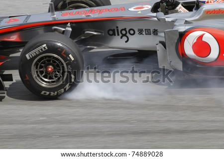 SEPANG, MALAYSIA - APRIL 8: Jenson Button of Vodafone McLaren Mercedes brakes hard during PETRONAS Malaysian Grand Prix on April 8, 2011 in Sepang, Malaysia. The race will be held on April 10, 2011. - stock photo