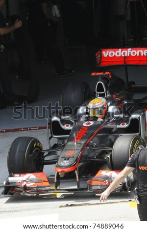 SEPANG, MALAYSIA- APRIL 8: Lewis Hamilton of Vodafone McLaren Mercedes exits garage during PETRONAS Malaysian Grand Prix on April 8, 2011 in Sepang, Malaysia. The race will be held on April 10, 2011. - stock photo