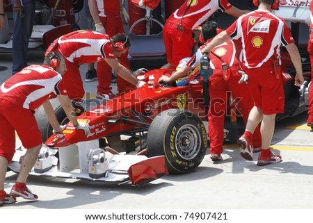 SEPANG, MALAYSIA -APRIL 8:Mechanics attend to Fernando Alonso of Scuderia Ferrari Marlboro at PETRONAS Malaysian Grand Prix on April 8, 2011 in Sepang, Malaysia.The race will be held on April 10, 2011