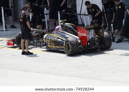 SEPANG, MALAYSIA - APRIL 8:Mechanics attend to Vitaly Petrov of Lotus Renault GP during practice at PETRONAS Malaysian GP on April 8, 2011 in Sepang, Malaysia.The race will be held on April 10 - stock photo