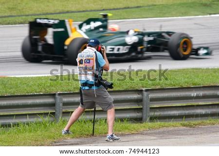 SEPANG, MALAYSIA - APRIL 8: Media photographer captures Jarno Trulli of Team Lotus as he races on the tracks during the Petronas Malaysian F1 Grand Prix on April 8, 2011 Sepang, Malaysia. - stock photo