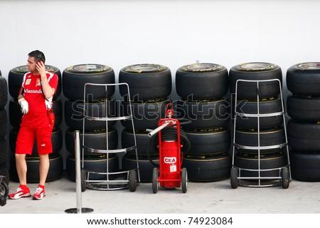 SEPANG, MALAYSIA - APRIL 8: Scuderia Ferrari F1 pit crew prepares the tires for the practice and qualifying runs of the Petronas Malaysian F1 Grand Prix on April 8, 2011 Sepang, Malaysia. - stock photo