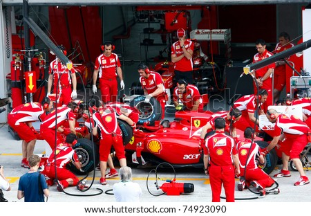 SEPANG, MALAYSIA - APRIL 8: Scuderia Ferrari F1 Team pit crew practice tire change in the pit-lane on the first practice day of the Petronas Malaysian F1 Grand Prix on April 8, 2011 Sepang, Malaysia. - stock photo