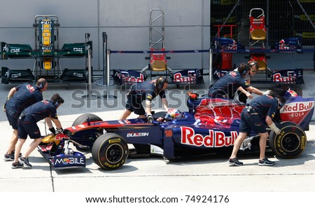 SEPANG, MALAYSIA - APRIL 8: Scuderia Toro Rosso pit crew works on Sebastien Buemi's car during pit-stop on the practice day of the Petronas Malaysian F1 Grand Prix on April 8, 2011 Sepang, Malaysia. - stock photo