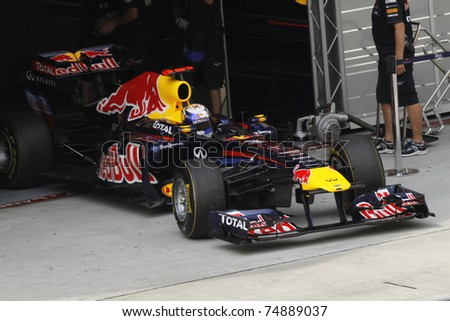 SEPANG, MALAYSIA - APRIL 8: Sebastian Vettel of Red Bull Racing exits garage during PETRONAS Malaysian Grand Prix on April 8, 2011 in Sepang, Malaysia. The race will be held on Sunday April 10, 2011. - stock photo