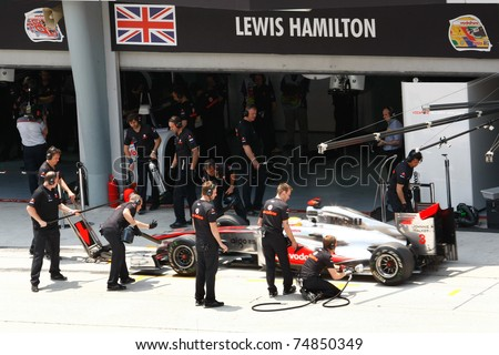 SEPANG, MALAYSIA - APRIL 8: Vodafone McLaren Mercedes' mechanics practice pit stops on Lewis Hamilton's car on practice day of the Petronas Malaysian F1 Grand Prix on April 8, 2011 in Sepang, Malaysia. - stock photo