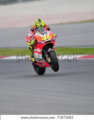 SEPANG, MALAYSIA-FEB 24: Valentino Rossi of Ducati Marlboro Team does a wheelie at MotoGP Official Test Sepang 2 on Feb 24, 2011 in Sepang, Malaysia. - stock photo