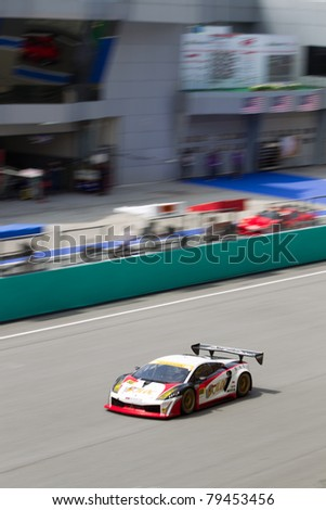 SEPANG, MALAYSIA - JUNE 18: A portrait view of Team Jloc in their Lamborghini going past the pit lane during qualifying at Super GT International series June 18, 2011 in Sepang, Malaysia - stock photo
