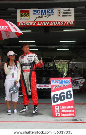 SEPANG, MALAYSIA-JUNE 20 : Bomex Porsche car 666 lead driver Mr. J. Yamashita taking picture with spectator at team garage. Super GT car race on June 20, 2010 in Sepang Circuit, Malaysia. - stock photo