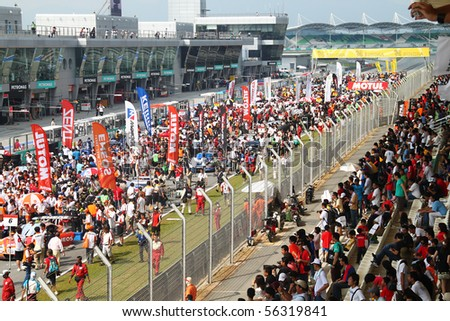 SEPANG, MALAYSIA-JUNE 20 : Huge crowd at the main grandstand and on the race track of Super GT car race on June 20, 2010 in Sepang Circuit, Malaysia.