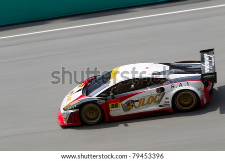 SEPANG, MALAYSIA - JUNE 18: Team Jloc in their Lamborghini going past the pit lane during qualifying at Super GT International series June 18, 2011 in Sepang, Malaysia - stock photo