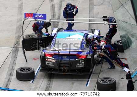 SEPANG, MALAYSIA - JUNE 19: Team Kunimitsu's pit-crew works on the car during pit-stop at the Sepang International Circuit before the Japan SUPER GT Round 3 race on June 19, 2011 in Sepang, Malaysia. - stock photo