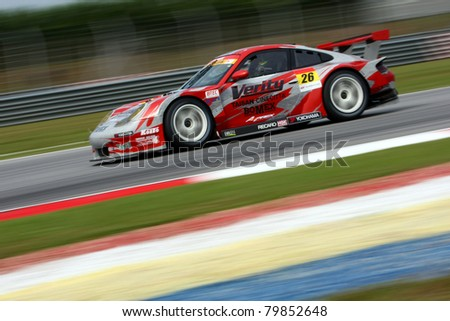 SEPANG, MALAYSIA - JUNE 18: The Porsche car of Team Taisan Cinecitta speeds on the straights of the Sepang International Circuit at the Japan SUPER GT Round 3 on June 18, 2011 in Sepang, Malaysia. - stock photo