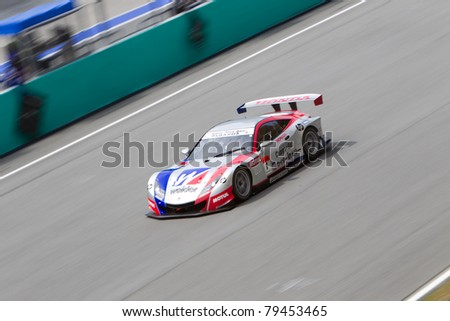 SEPANG, MALAYSIA - JUNE 18: Weider Honda Racing team goes past the pit lane during qualifying at Super GT International series June 18, 2011 in Sepang, Malaysia. Weider took pole position - stock photo